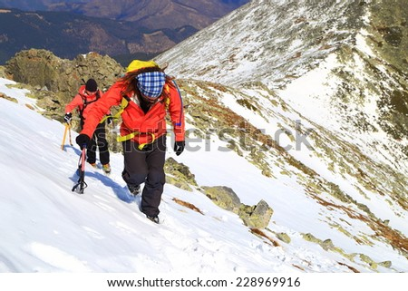 Climbers traversing steep snow covered mountain face in winter - stock photo