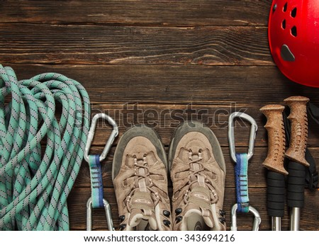 climbing and hiking equipment: blue rope, red helmet, grey shoes and other set  on dark wooden background, top view - stock photo