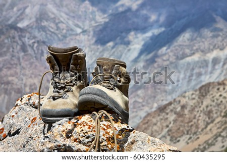 Climbing boots on the rock in the mountains - stock photo