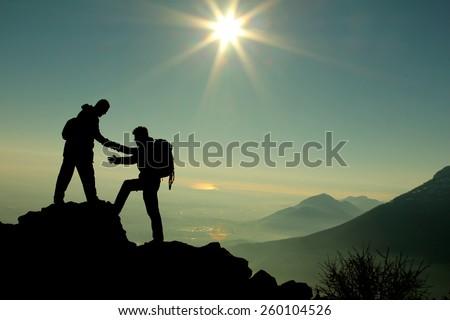 climbing help & sunrise at the summit - stock photo