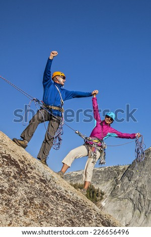 Climbing team celebrate on the summit of a challenging ascent. - stock photo
