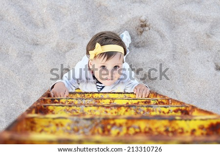 Climbing the ladder baby girl - stock photo