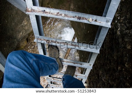 climbing the ladder over the abyss - stock photo