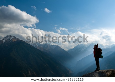 Climbing young adult at the top of summit with aerial view of the blue sky - stock photo