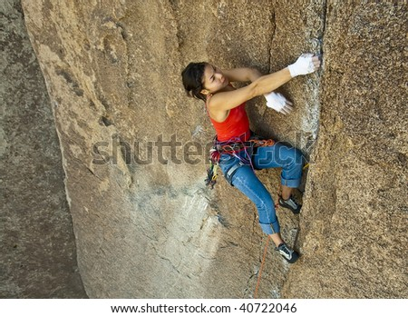 Clinging to an overhang a female climber is focused on her next move as she battles her way up a steep crack in Joshua Tree National Park, California. - stock photo