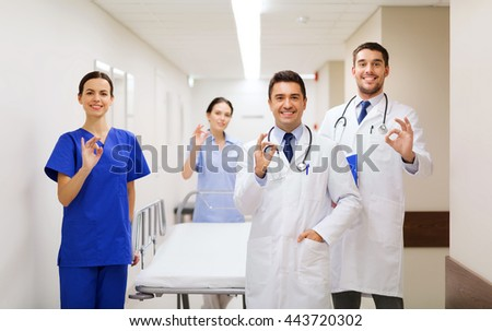 clinic, profession, people, health care and medicine concept - group of happy medics or doctors with gurney showing ok hand sign at hospital corridor - stock photo