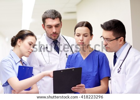 clinic, profession, people, health care and medicine concept - group of medics or doctors with clipboard at hospital corridor