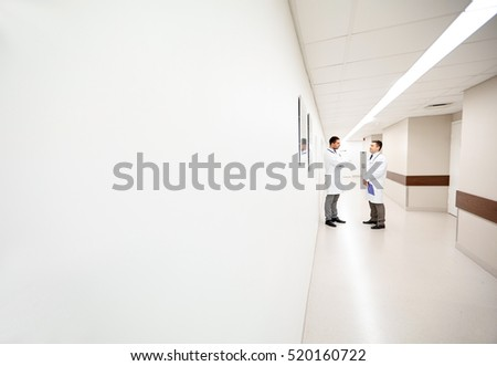 clinic, profession, people, healthcare and medicine concept - male doctors talking at hospital corridor