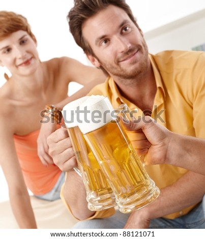 Clinking beer glasses, having party.? - stock photo