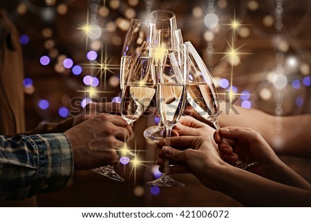 Clinking glasses of champagne in hands on bright lights background with snow effect - stock photo