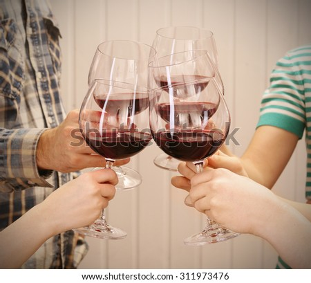 Clinking glasses of red wine in hands on color wooden planks background