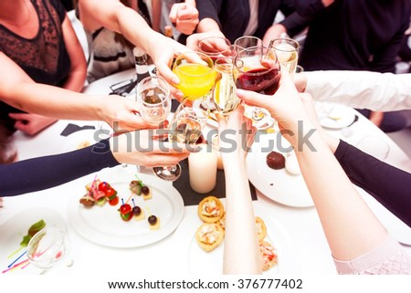 Clinking glasses with alcohol and toasting, party. Congratulations to the event. Cheerful party friends - stock photo