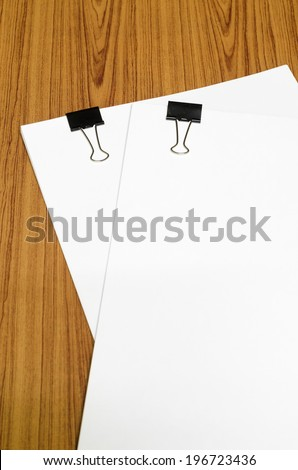 clip and paper on wood background - stock photo