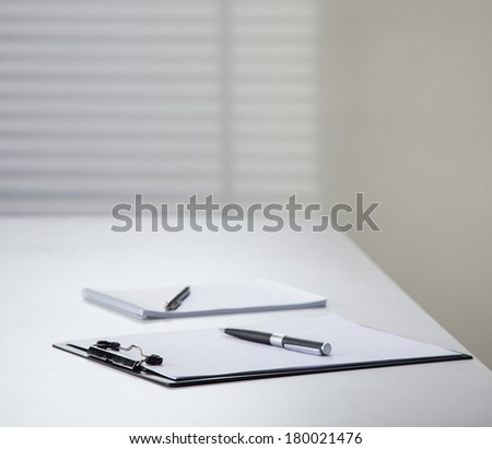 Clipboard and notebook with pens on a table in the office - stock photo