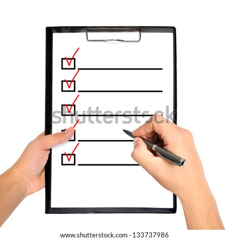 clipboard with checklist in hand - stock photo