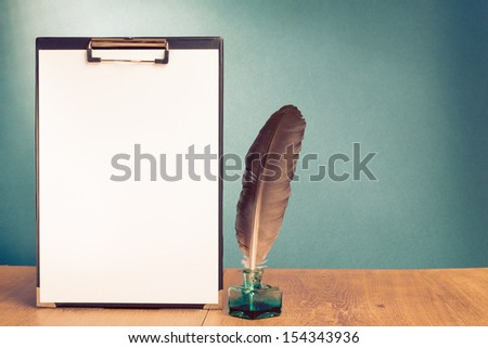 Clipboard with paper, quill pen and inkwell on table for vintage background - stock photo