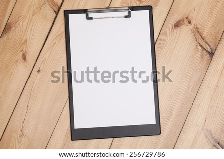 clipboard with white sheet on wooden floor - stock photo