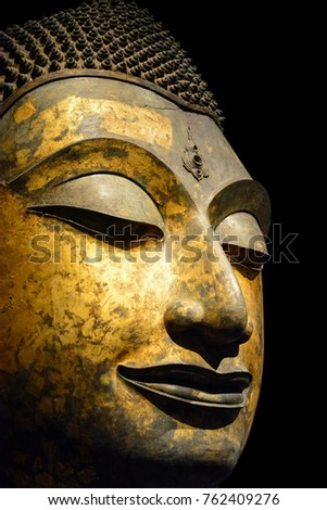 clipping path, close up of antique bronze Buddha face isolated on black background (selective focus)