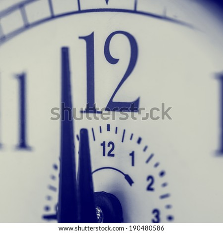 Clock about to strike 12 midnight or midday , closeup retro effect view with focus to the two digits of the number 12 and shallow dof, possibly conceptual of New Year. - stock photo