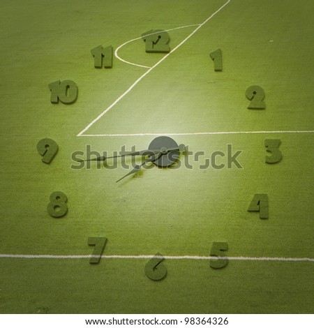 Clock and football field background - stock photo