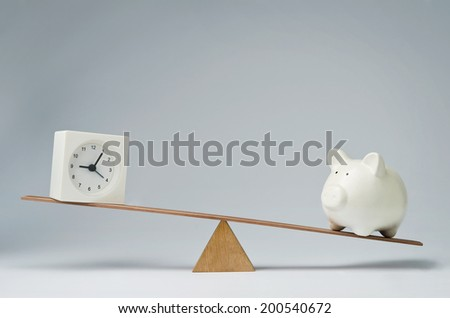 Clock and piggy bank balancing on a seesaw - stock photo