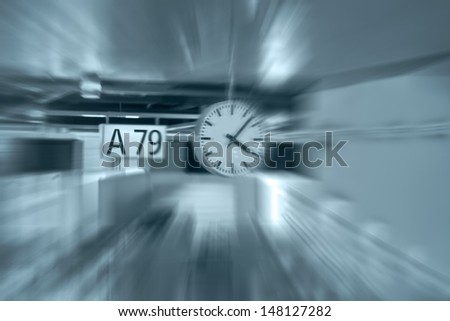 Clock and signboard in futuristic gate of the airport transfer. Radial blur.  - stock photo