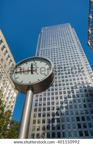 Clock and skyscrapers at Canary Wharf, Docklands the heart of the financial district of London - stock photo