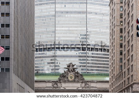 Clock and statue on grand central station in new york city with office building in the background - stock photo
