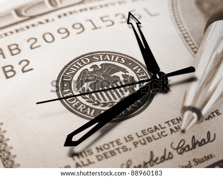 Clock and symbol of Federal reserve system on dollar. Finance concept.