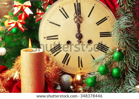 Clock, burning candle and christmas decorations