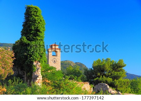 Clock church tower surrounded by green Mediterranean vegetation and ruins - stock photo
