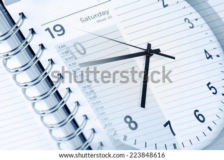 Clock face and diary page - stock photo