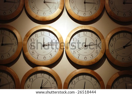 clock faces arranged on white wall