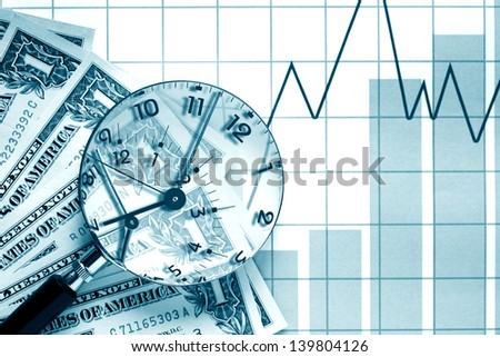 Clock inside magnifying glass near money on paper background with chart - stock photo