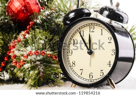 clock on snow under decorated christmas tree - stock photo