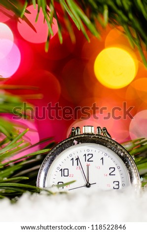 clock on snow with christmas tree branch on blurred background - stock photo