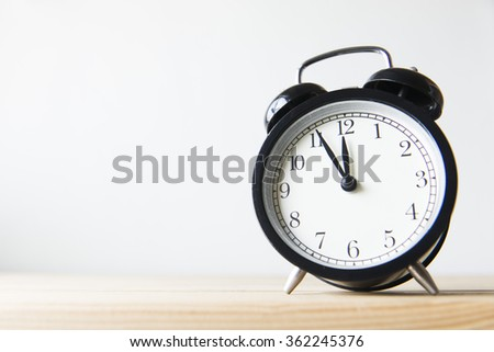 Clock on the wooden table on white background