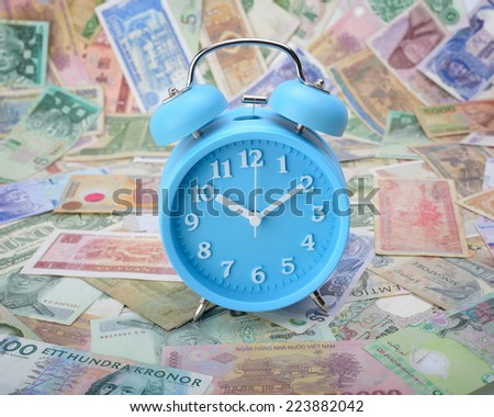 Clock on world currency - stock photo