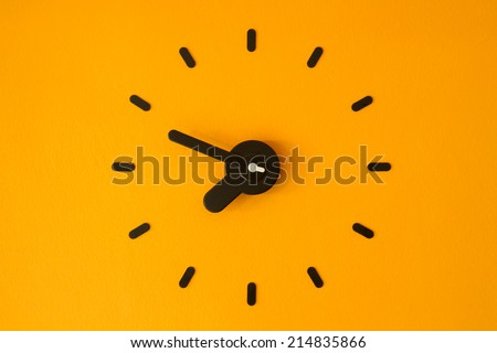 Clock on yellow wall - stock photo