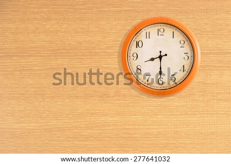 Clock showing 8:30 o'clock on a wooden wall - stock photo