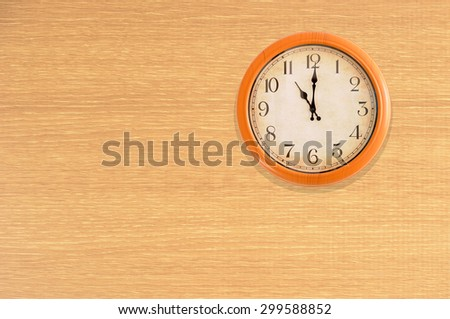 Clock showing 11 o'clock on a wooden wall - stock photo