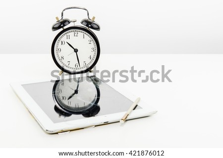 Clock winding and tablet with a broken screen on white background. - stock photo