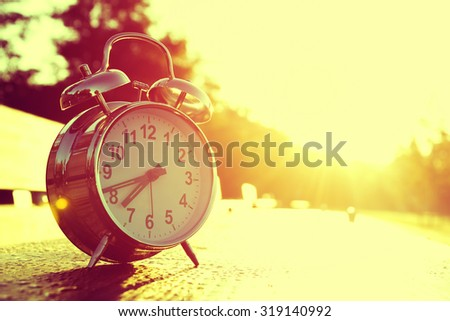 Clock with Rising Sun Behind - stock photo