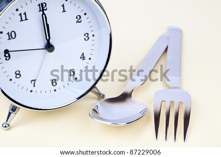 Clock with some silverware on the table - stock photo