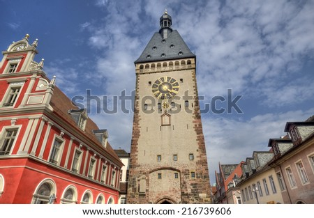 Clocktower and red house in the historical center of the city of Speyer in Germany - stock photo