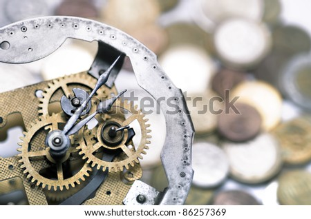 clockwork with defocused coins in the background