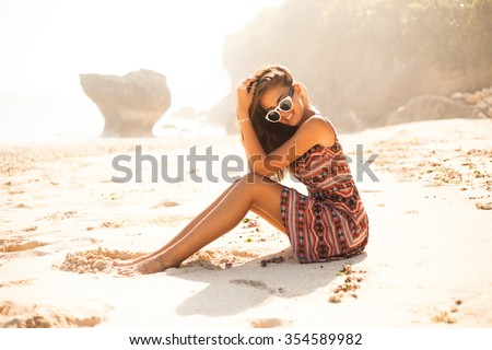 cloe-up image of boho style young woman relaxing on the beach wear her shirt dress with abstract print,boho chic,style and beauty,fashionable girl,accessory store,secret beach,bali,indonesia,trendy - stock photo