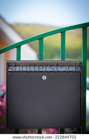 Cloes up of a mailbox on the street with fence - stock photo