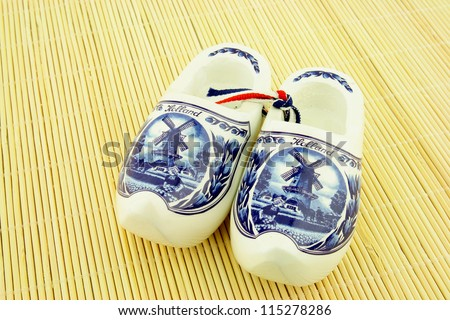 Clogs or wooden shoes, traditional Dutch footwear. Used by farmers. With a general print of a windmill and tulips. - stock photo