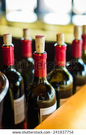 Close color shot of red wine bottles lined up in a row with corks showing at a winery in paso robles, ca.  - stock photo